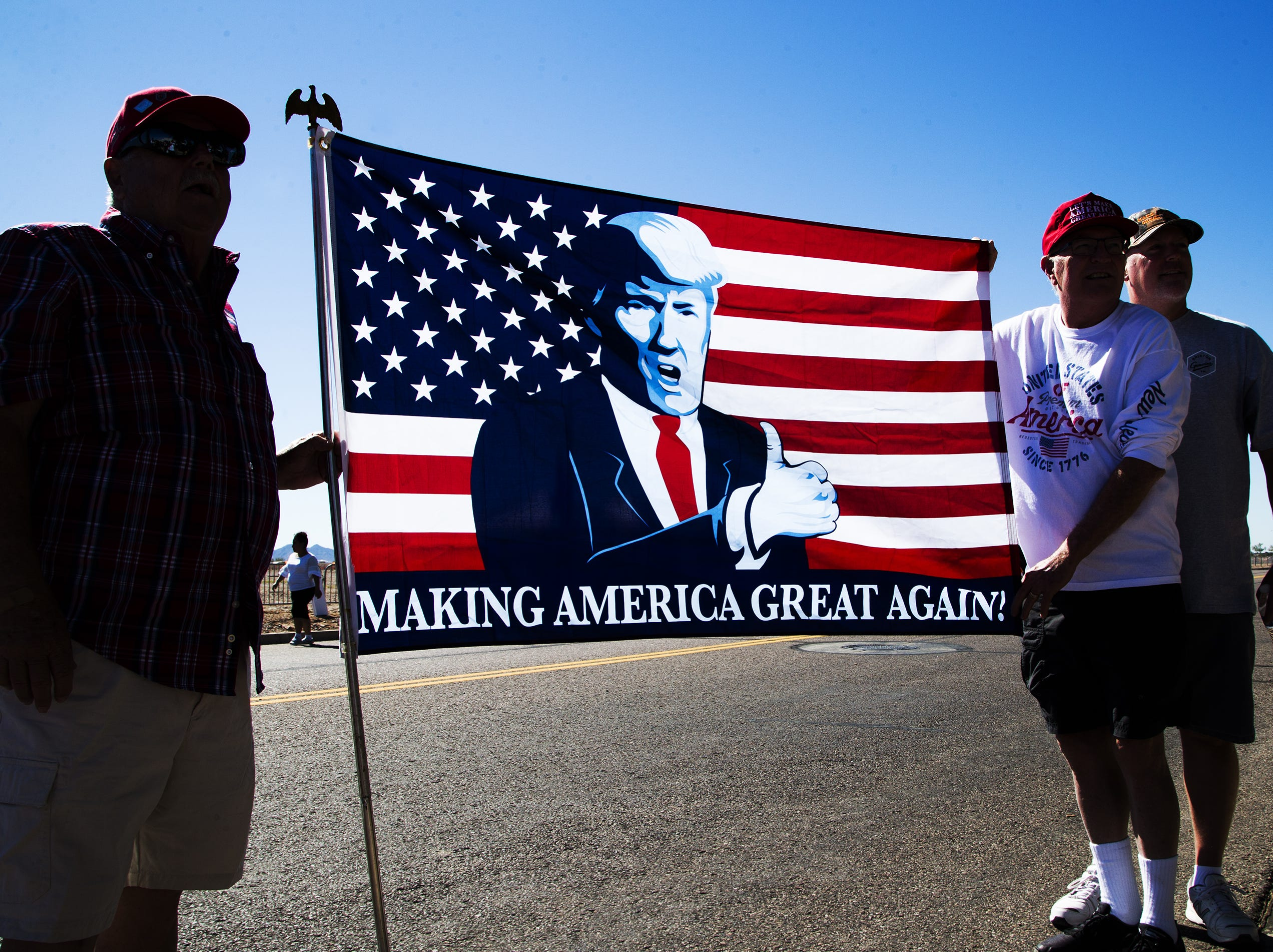 Fans of President Donald Trump show their flag while waiting in line to enter the International Air Response Hangar at Williams Gateway Airport on Oct. 19, 2018. Trump is set to appear Friday evening for a rally supporting Senate candidate Rep. Martha McSally.