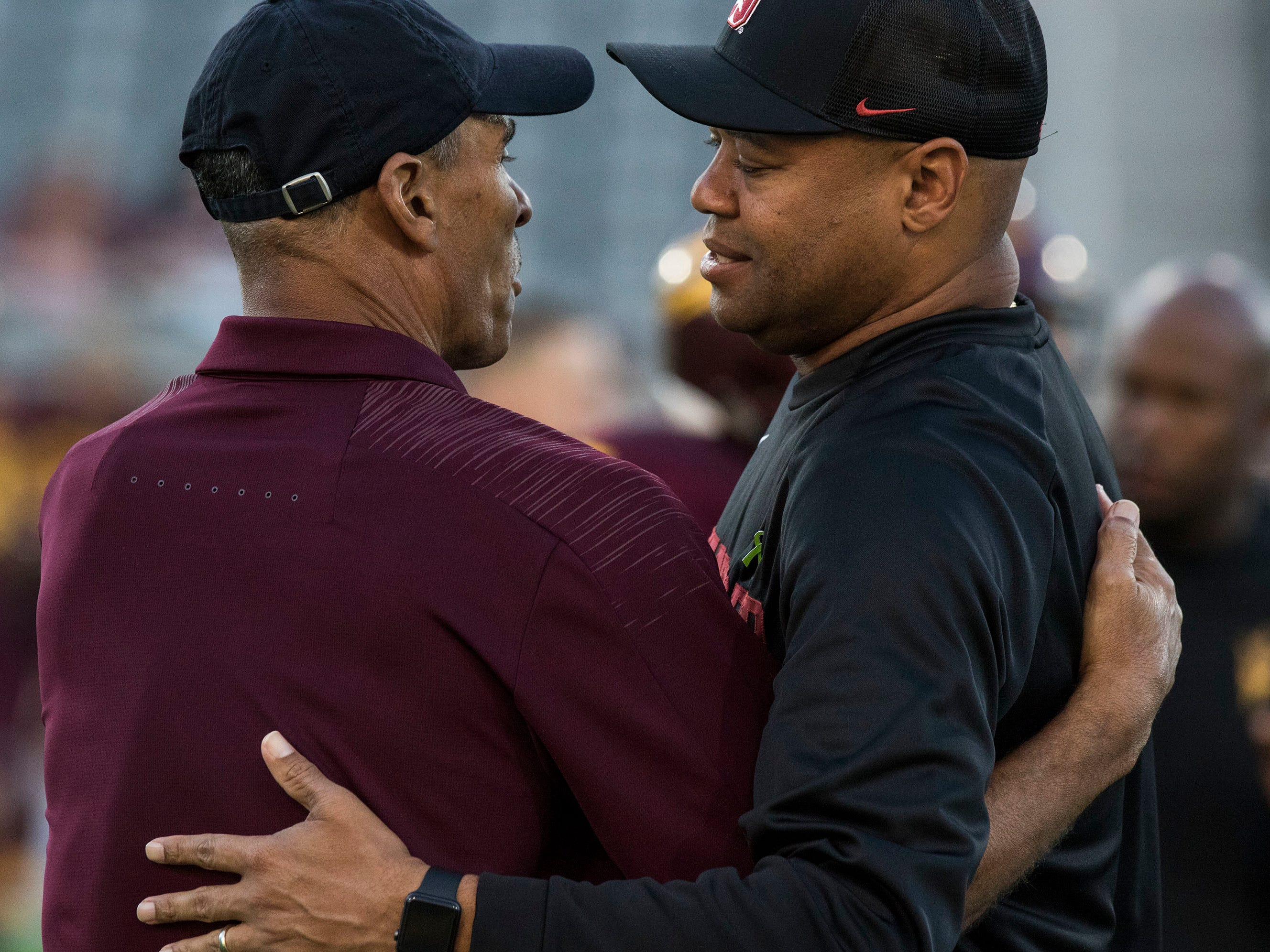 Arizona State head coach Herm Edwards, left, and Stanford head coach Dave Shaw hug before the first half of an NCAA college football game Thursday, Oct. 18, 2018, in Tempe, Ariz.