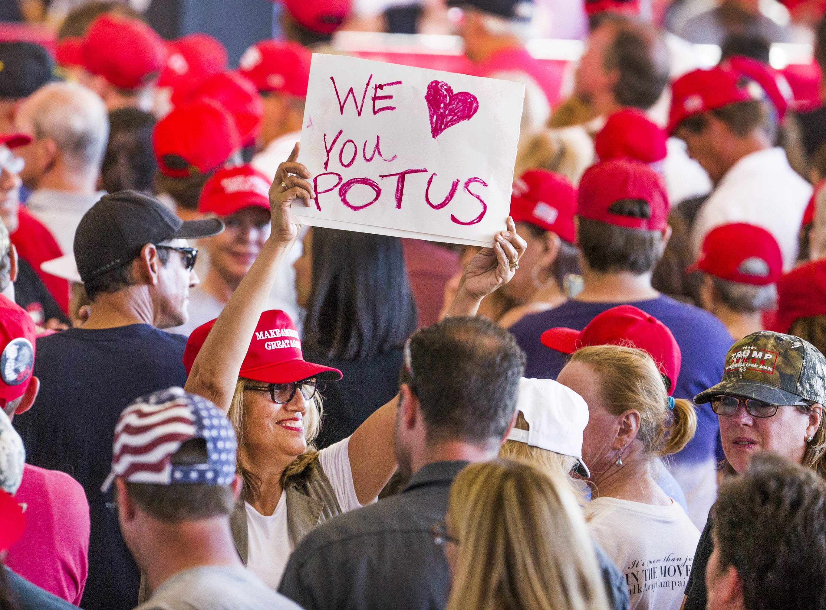 A woman waves a sign inside the International Air Response Hangar at Phoenix Mesa Gateway Airport on Oct. 19, 2018. The crowd had several hours to wait for President Donald Trump to appear Friday evening for a rally supporting Senate candidate Martha McSally.