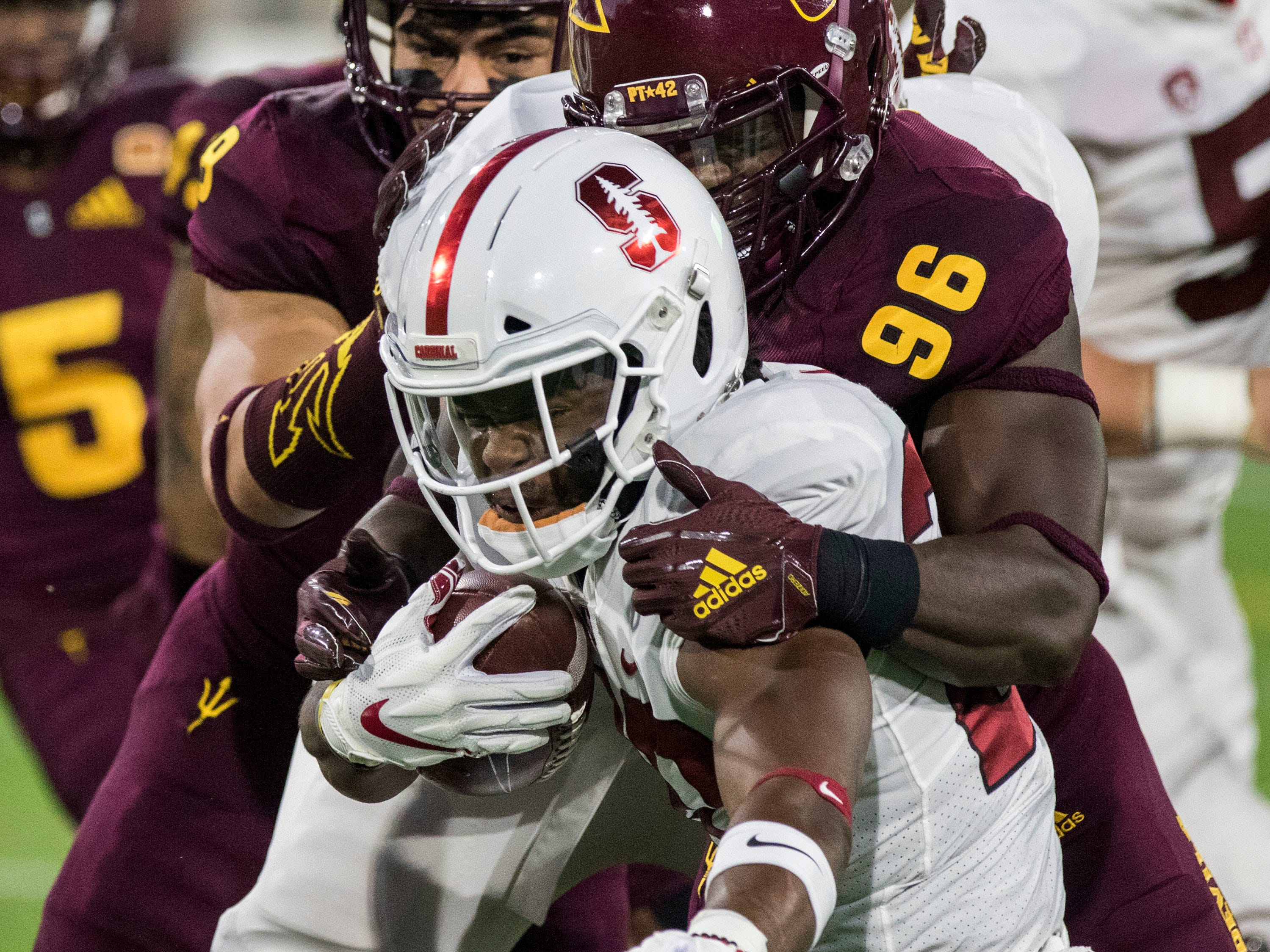 Stanford's Bryce Love gets wrapped up by Arizona State's Jalen Bates during the first half of an NCAA college football game Thursday, Oct. 18, 2018, in Tempe, Ariz.