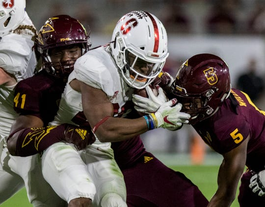 Stanford's Bryce Love gets stuffed at the line by Arizona State's Tyler Johnson (41) and Kobe Williams (5) during the first half of an NCAA college football game Thursday, Oct. 18, 2018, in Tempe, Ariz.