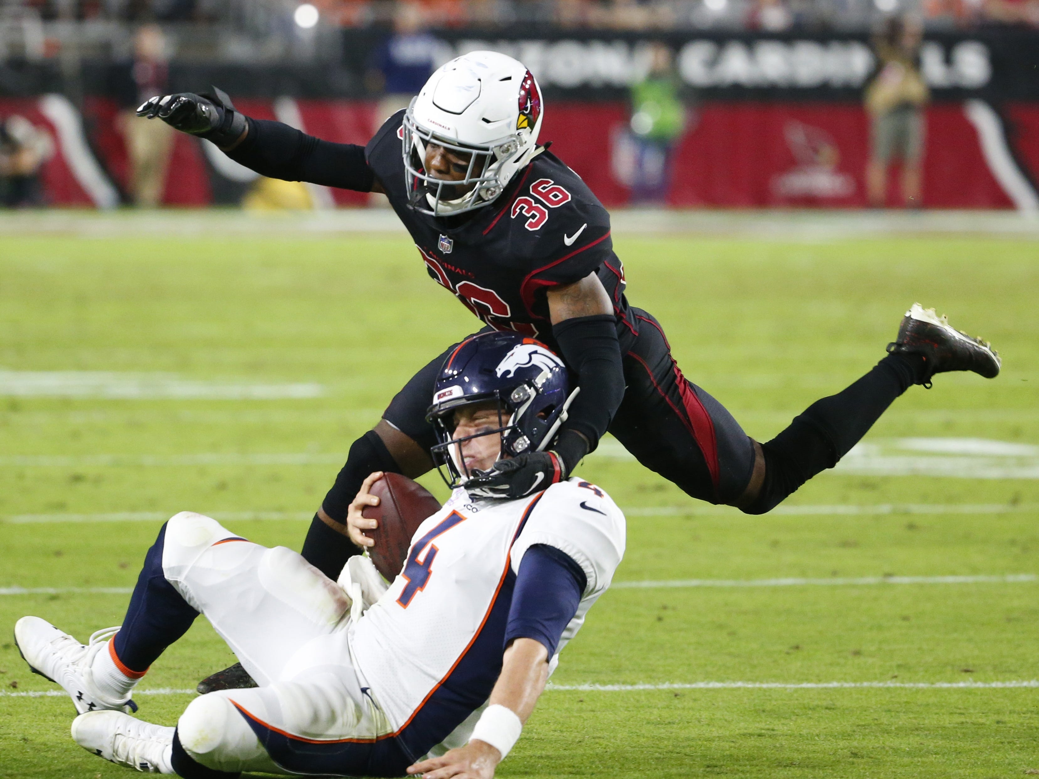 Arizona Cardinals strong safety Budda Baker (36) tackles Denver Broncos quarterback Case Keenum (4) during a football game at State Farm Stadium in Glendale on October 18, 2018.