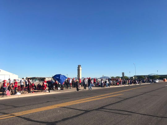 About 100 people are lined up outside the International Air Response hangar in Mesa on Oct. 19, 2018, waiting for President Trump's rally.