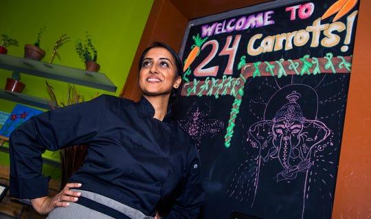 "Sasha Raj, the self-proclaimed ""vegan superhero,"" poses in at her restaurant, 24 Carrots in Tempe, Wednesday, October 17, 2018."