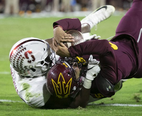 ASU quarterback Manny Wilkins lands in th end zone after scoreing a touchdown on the run as Stanford linebacker Bobby Okereke attempted the tackle during the  fourth quarter of the Pac-12 college football game at Sun Devil Stadium in Tempe on October 18, 2018.