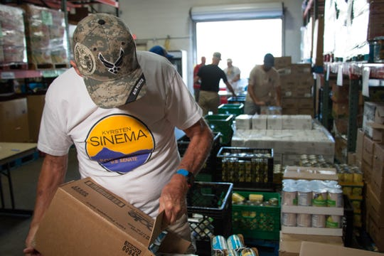Vic Peterson, a member of Veterans for Sinema, refills cans at a volunteer event the candidate at Desert Mission Food Bank, October 19, 2018.