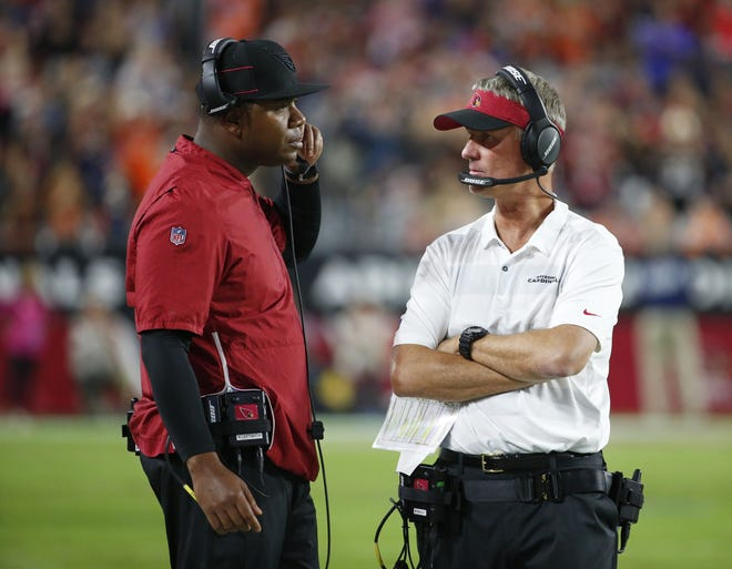 Arizona Cardinals quarterback coach Byron Leftwich, left, talks with offensive coordinator Mike McCoy on the sidelines during a football game against the Denver Broncos at State Farm Stadium in Glendale on October 18, 2018.