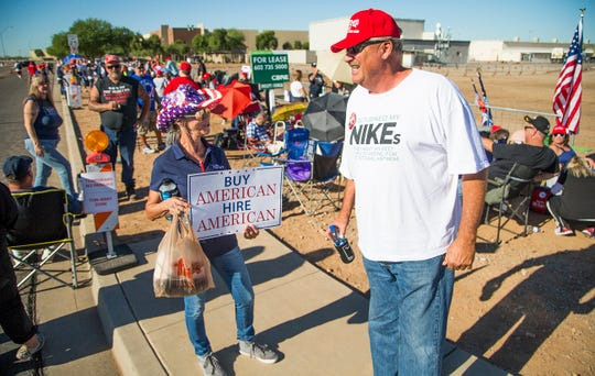 Sheridan Beaulieu of Florence and Bryan Harmon of Prescott wait in line to enter the International Air Response Hangar at Phoenix-Mesa Gateway Airport Oct. 19, 2018. President Donald Trump will appear Friday evening for a rally supporting Senate candidate Rep. Martha McSally.