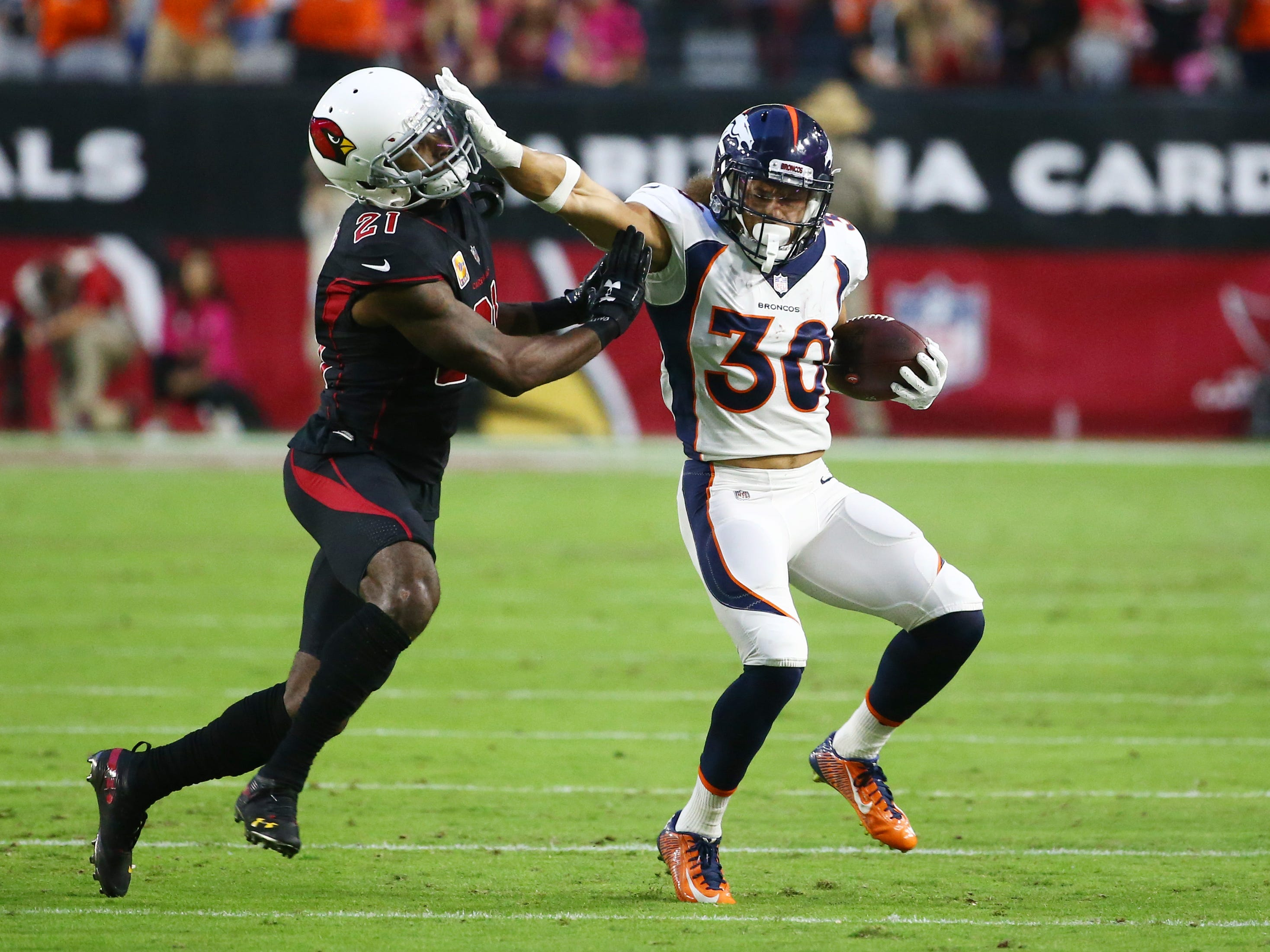 Denver Broncos running back Phillip Lindsay pushes away Arizona Cardinals Patrick Peterson in the first half at State Farm Stadium in Glendale, Ariz.