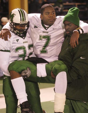 Marshall quarterback Byron Leftwich (7) is carried from the field after Akron's 34-20 win Saturday, Nov. 2, 2002, in Akron, Ohio. Leftwich injured his leg in the first quarter and came back in the game in the third quarter.