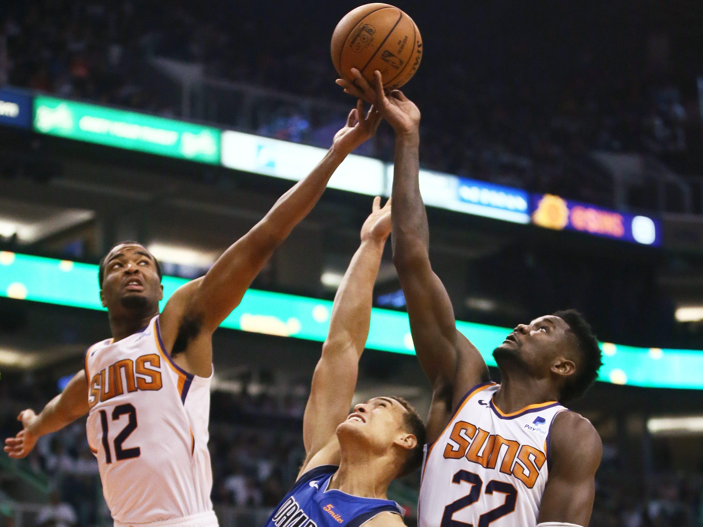 Phoenix Suns rookie center Deandre Ayton reaches for the rebound against Dallas Mavericks Dwight Powell during the season opener at Talking Stick Resort Arena on Oct. 17, 2018, in Phoenix, Ariz.