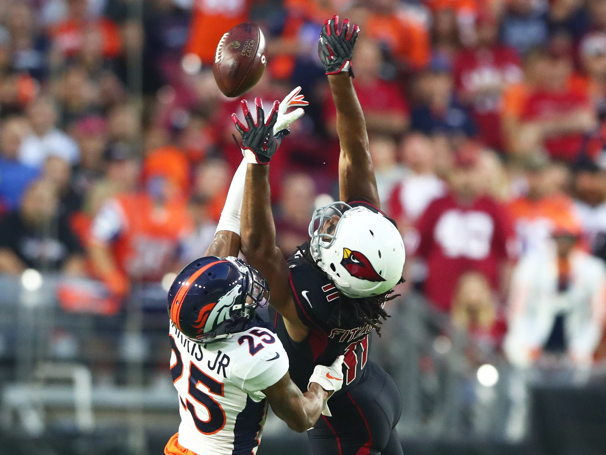Oct 18, 2018; Glendale, AZ, USA; Arizona Cardinals wide receiver Larry Fitzgerald (11) is unable to catch an overthrown pass against Denver Broncos cornerback Chris Harris Jr. (25) in the first quarter at State Farm Stadium.