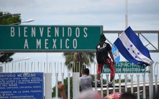 Un inmigrante hondureño salta la reja rumbo a México.