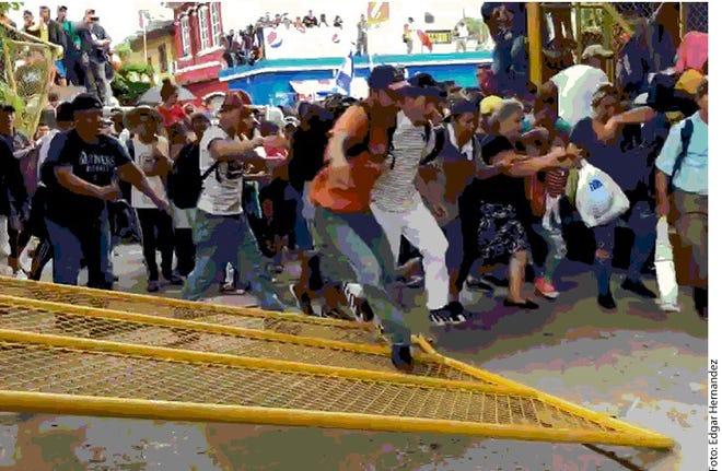 Migrantes centroamericanos cruzan en este momento el Puente Internacional de Suchiate hacia México.