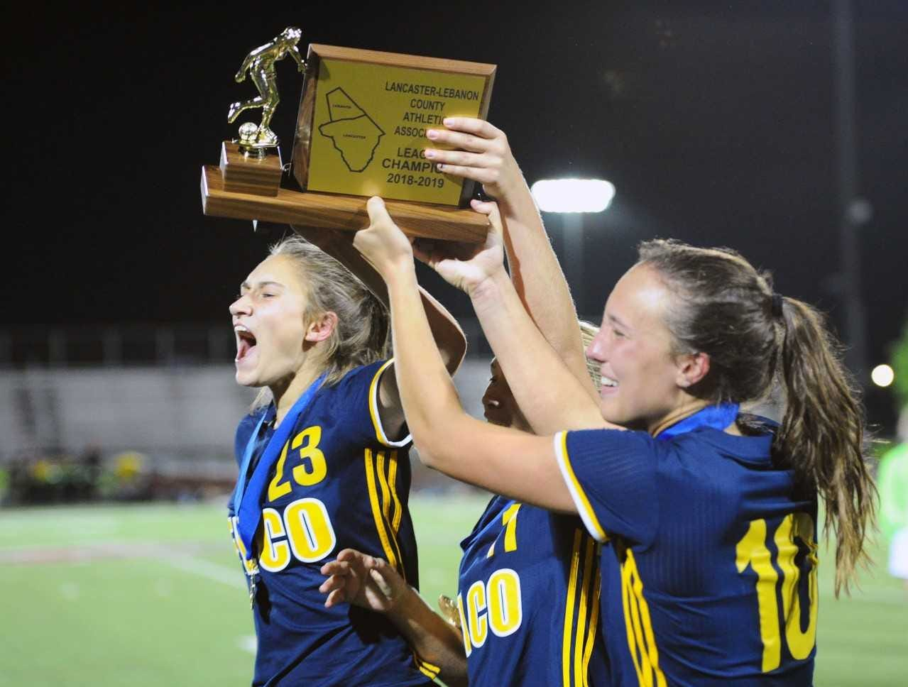 Elco captains, from left, Jordan Rosengrant, Julia Nelson and Ryelle Shuey raise the Lancaster-Lebanon League championship trophy following Thursday's 2-1 title game win over Conestoga Valley.