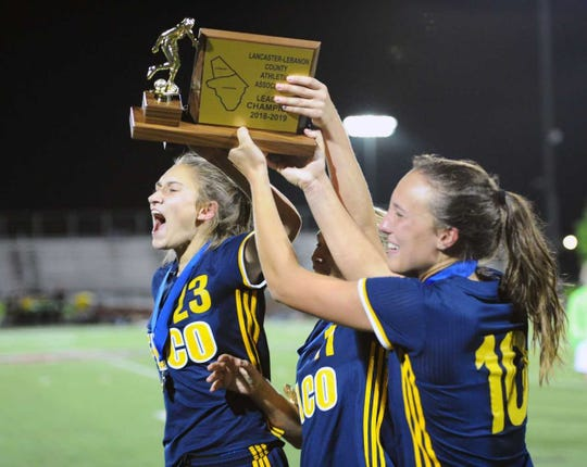 Elco captains, from left, Jordan Rosengrant, Julia Nelson and Ryelle Shuey raise the Lancaster-Lebanon League championship trophy following the Raiders' 2-1 title game win over Conestoga Valley.