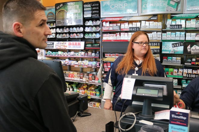 Phillip Adkins, left, buys a Mega Millions ticket from Heather Holmes at the FriendShip Food Store in Port Clinton as the jackpot hit $1 billion on Friday.