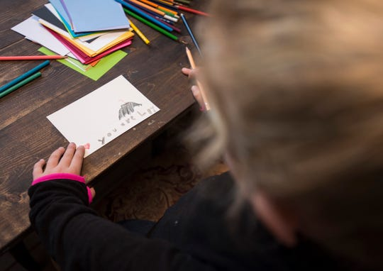 "Feenie Drum, 7, works on a postcard she is sending to a woman in Florida on Thursday, Oct. 18, 2018 in the dining room of her family's Algonac home. Feenie, known as ""The Postcard Princess"", makes and sends postcards to people in hopes of helping them to have a good day."