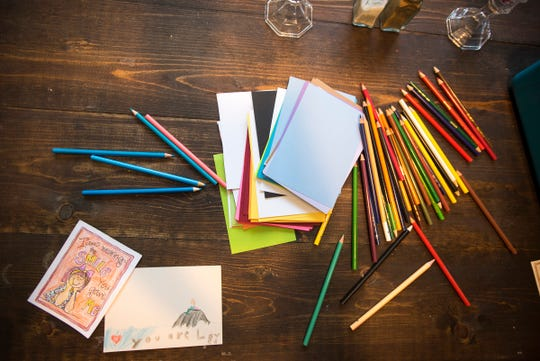 "Postcards made by 7-year-old Feenie Drum sit among other supplies on the dining room table of her family's Algonac home. Most of the cards Feenie makes are sent out-of-state for people nominated through her Facebook page, ""The Postcard Princess."""