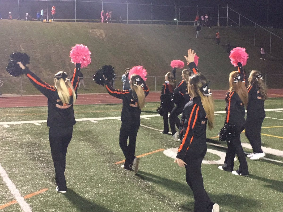 Northeastern cheerleaders wave to some fans before Friday night's football game against York High.
