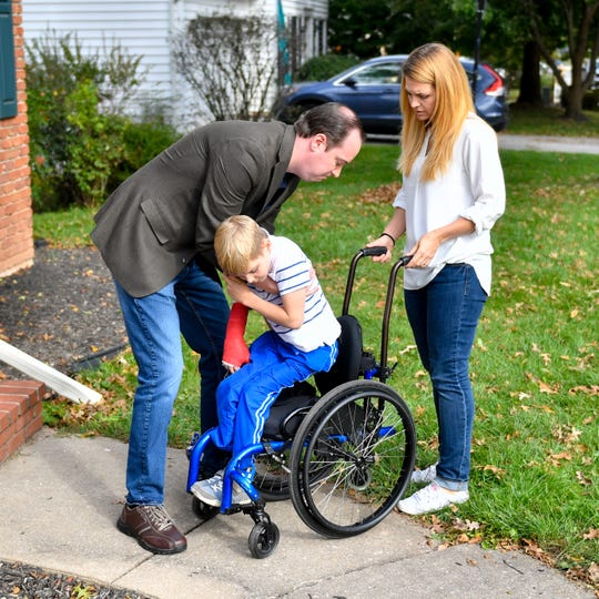 Sebastian Bottomley's father, Jarrod, and his mother, Christa, help him into his wheelchair so he can play outside, October 18, 2018.