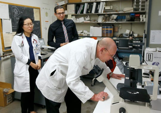Rochester Regional Health infectious disease specialist Dr. Emil Lesho looks into a microscope as residents Tara Chen and John Hanna look on. Lesho talked earlier to the media to clarify a case regarding a man who died after eating squirrel brains. They presented the case to a medical conference in October, and the story was picked up online and went viral.