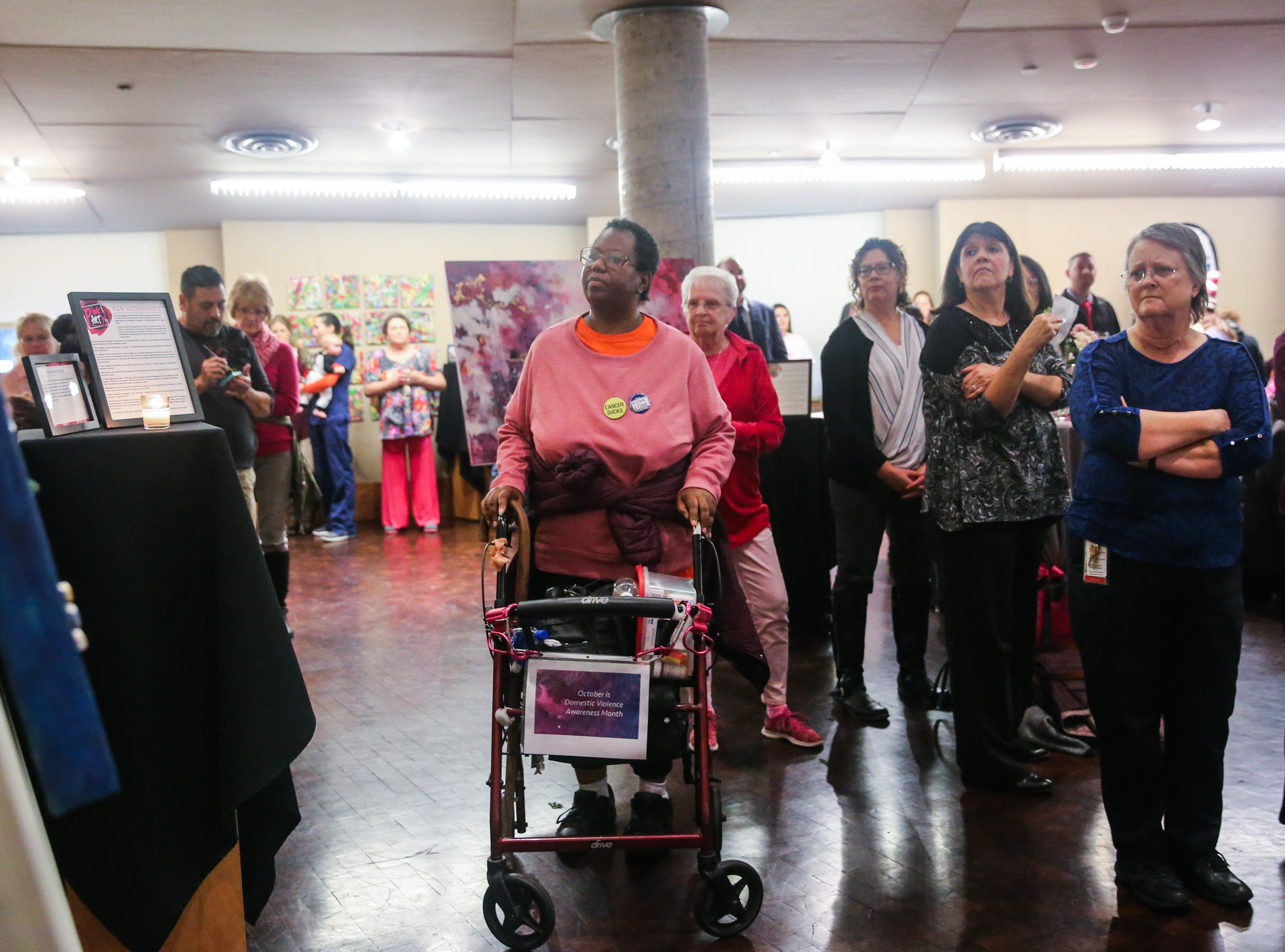 Attendees look over an artwork on display during Shannon's pink pARTy Thursday, Oct. 18, 2018, at San Angelo Museum of Fine Arts.