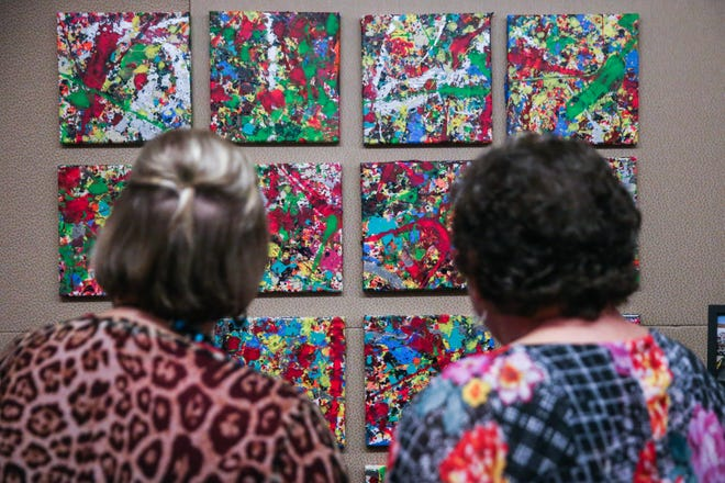 Amanda Terry, left, and Lorrie Bennett look over Expression of Survival class artwork they helped create during creates a tiny painting during Shannon's pink pARTy Thursday, Oct. 18, 2018, at San Angelo Museum of Fine Arts.