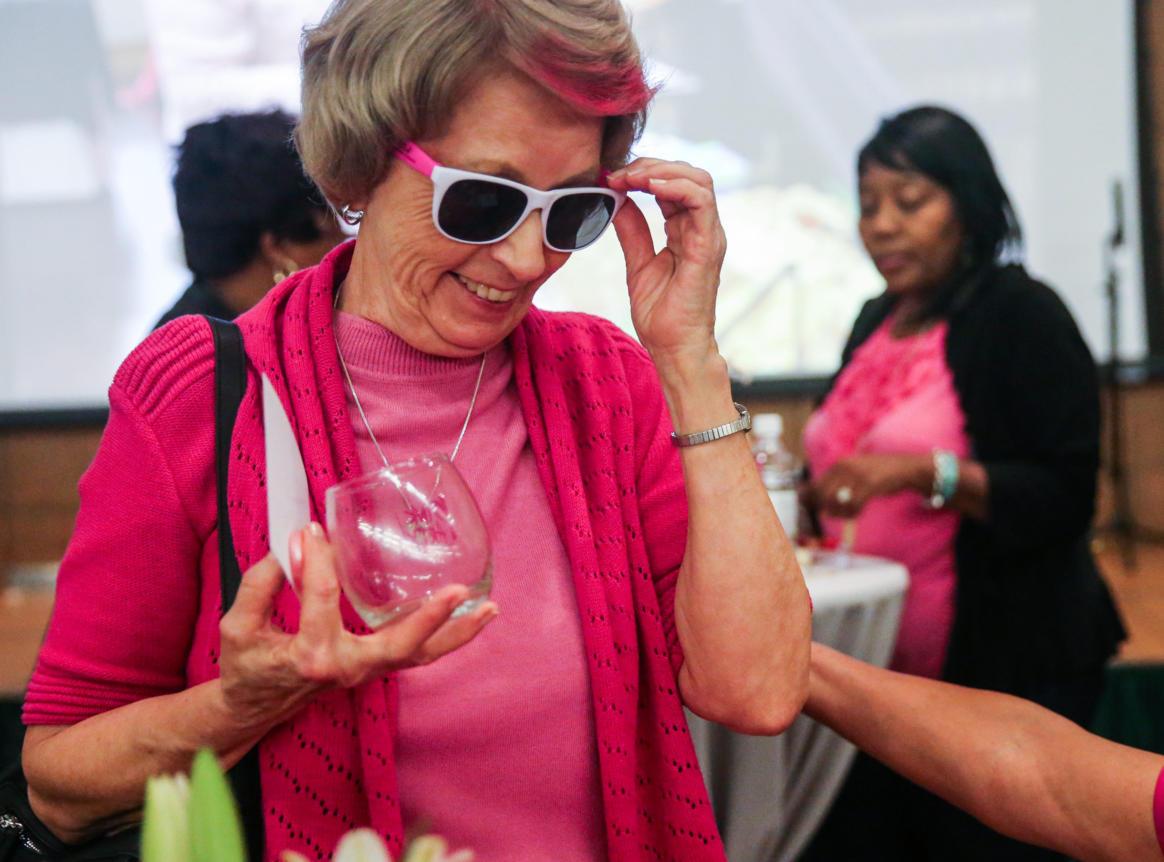 Pat Fennell tries on glasses she got at a booth during Shannon's pink pARTy Thursday, Oct. 18, 2018, at San Angelo Museum of Fine Arts.