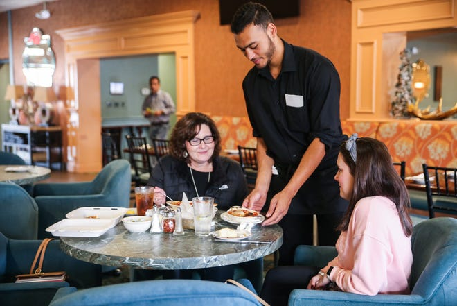 Randall Johnson serves Suzanne Gould, left, and Brynna Kinsey Friday, Oct. 19, 2018, at Napoli's Italian Restaurant.