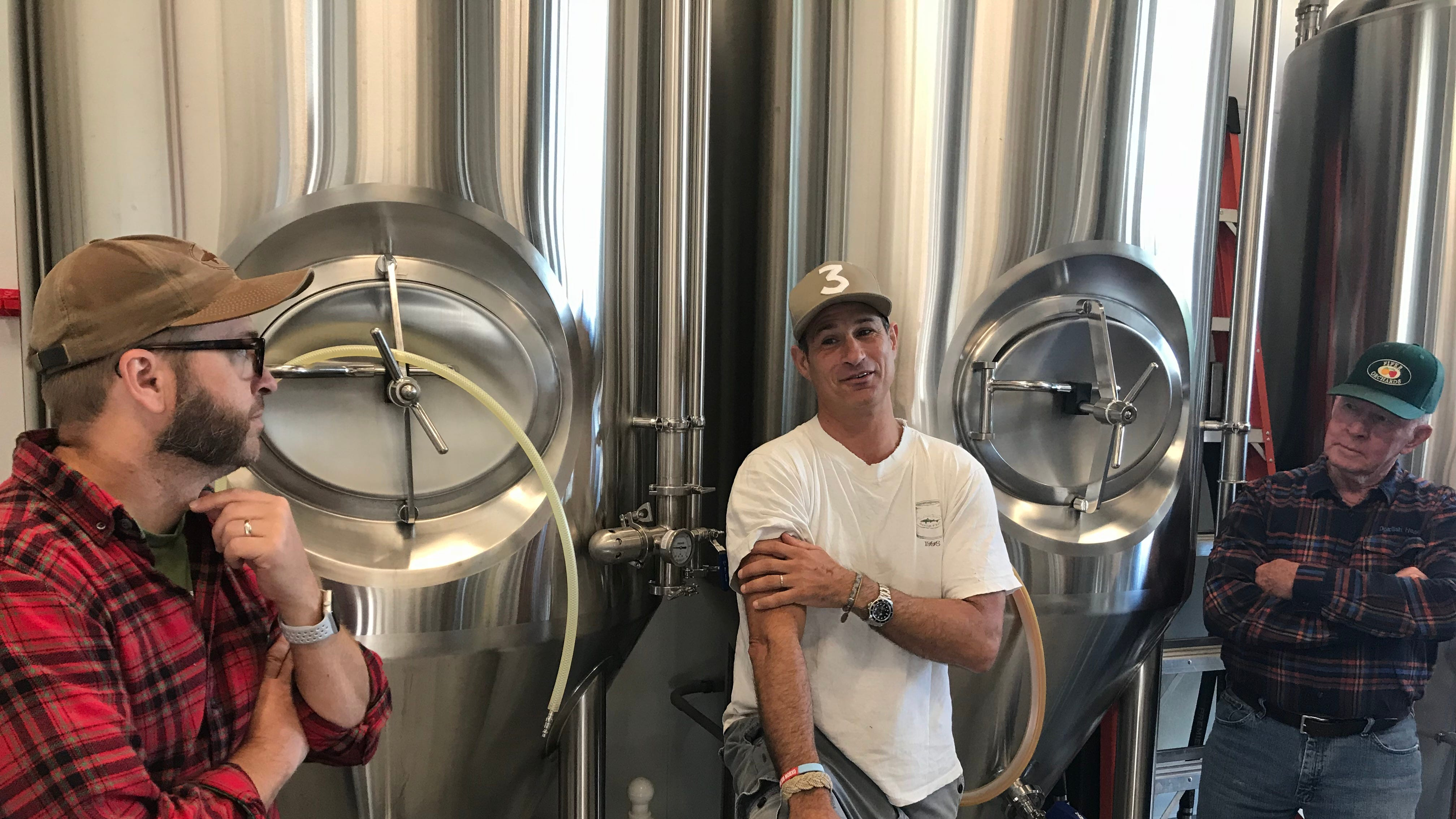 Bryan Selders (left), Sam Calagione (middle) and John Carter (right) discuss the apple cider doughtnut inspired beer Dogfish Head Craft Brewery and Dewey Beer Co. are creating in Rehoboth Beach on Oct. 18, 2018.
