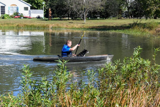 Mike Kitchen works with border collie Lotus to chase geese out of the pond at Ocean Pines on Friday, Oct 19, 2018.