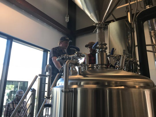 Michael Reilly (left) and Bryan Selders (right) work inside the brewhouse at Dogfish Head Brewings & Eats in Rehoboth Beach on Oct. 18, 2018.