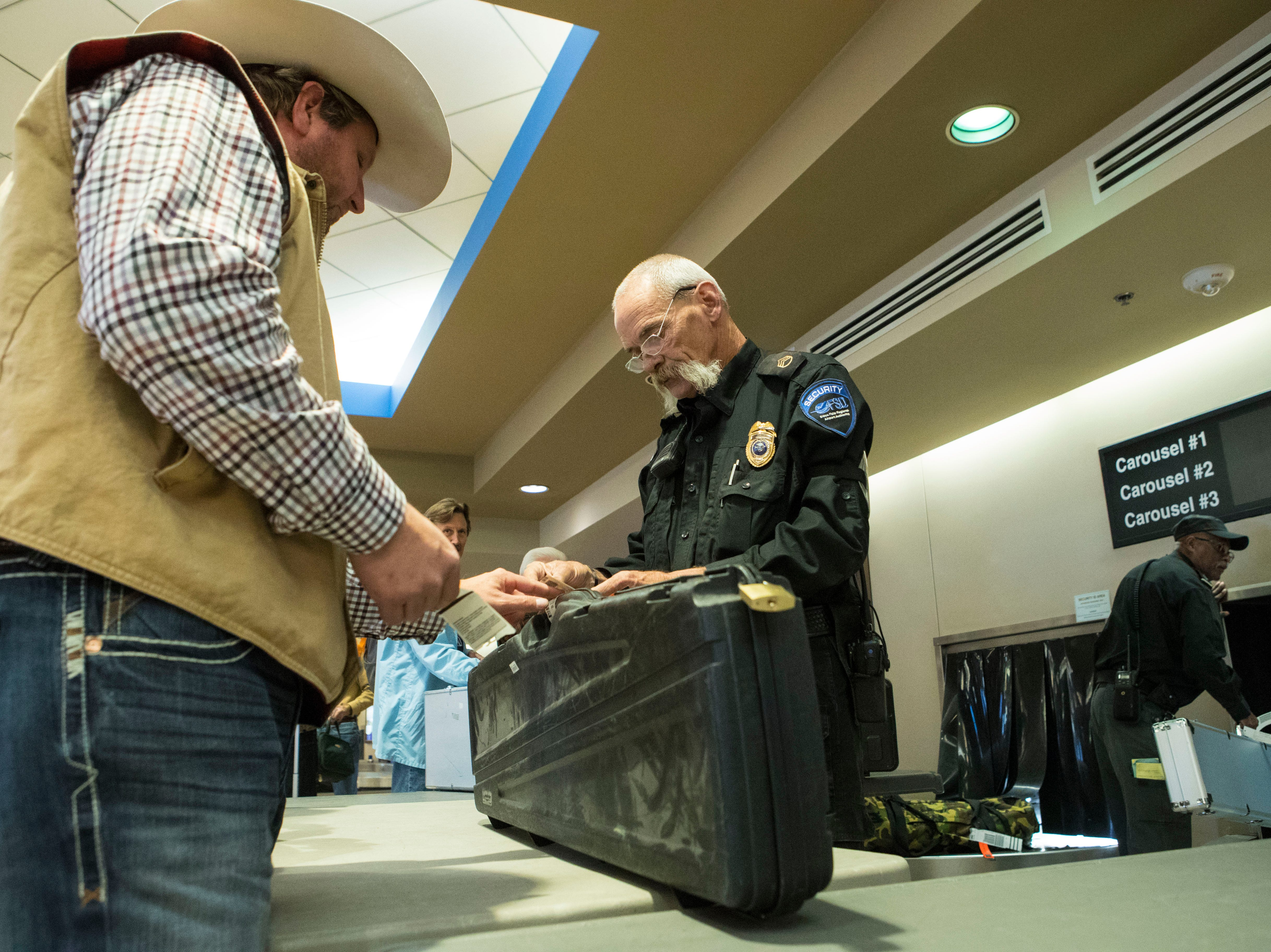 Dale Medlen, security supervisor, looks over Tyler Fischer's information before he gives him his gun at Sioux Falls Regional Airport Friday, Oct. 19, 2018.