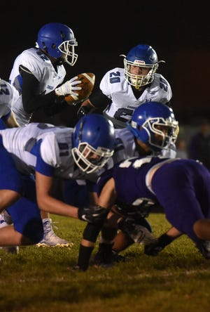 Sioux Falls Christian's Dawson Mulder (42) goes to hand the ball to Parker Nelson (20) during a game against Beresford Thursday, Oct. 18, 2018 in Beresford, S.D.