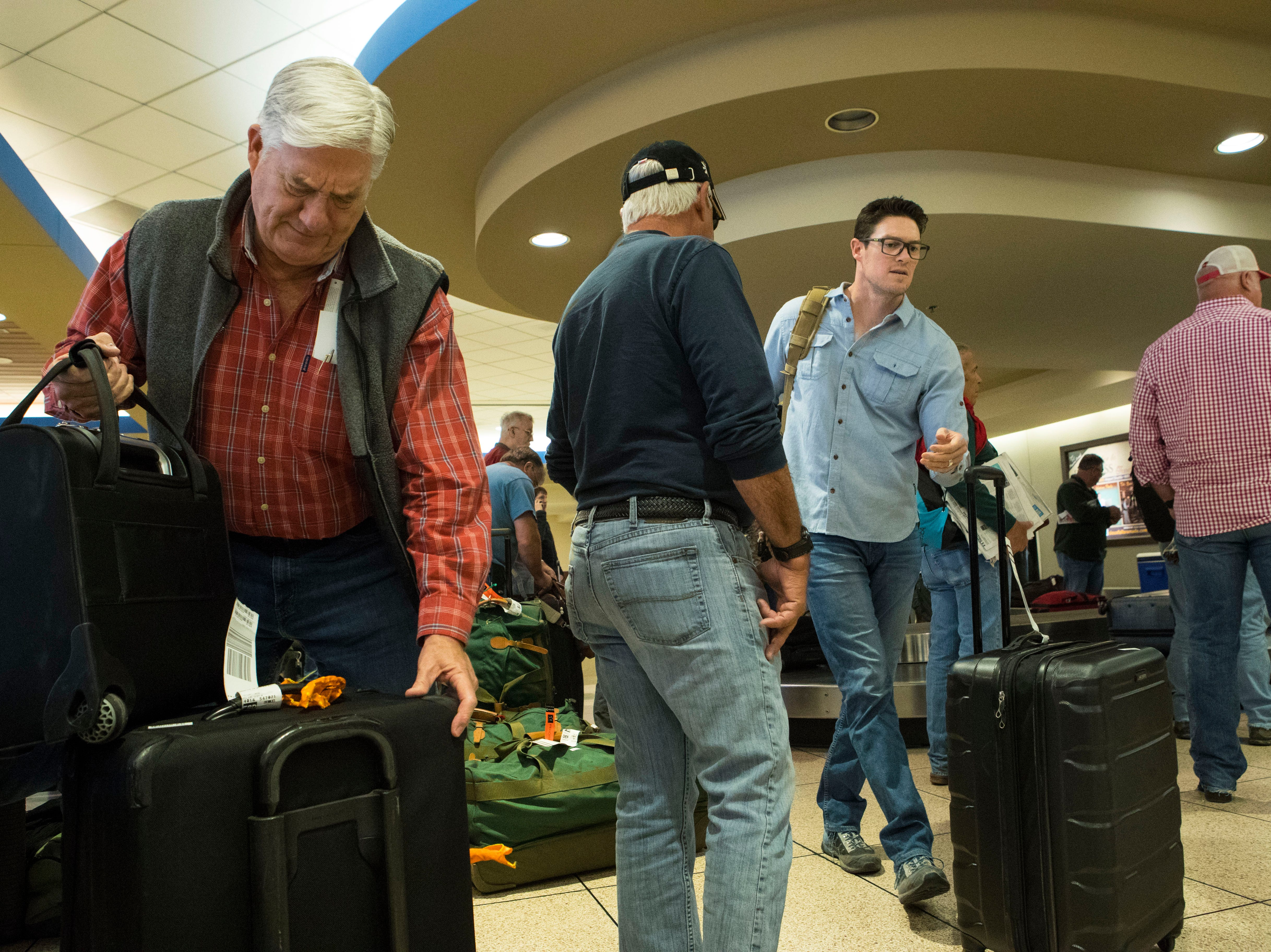 Pheasant hunters pick up their luggage at Sioux Falls Regional Airport Friday, Oct. 19, 2018.