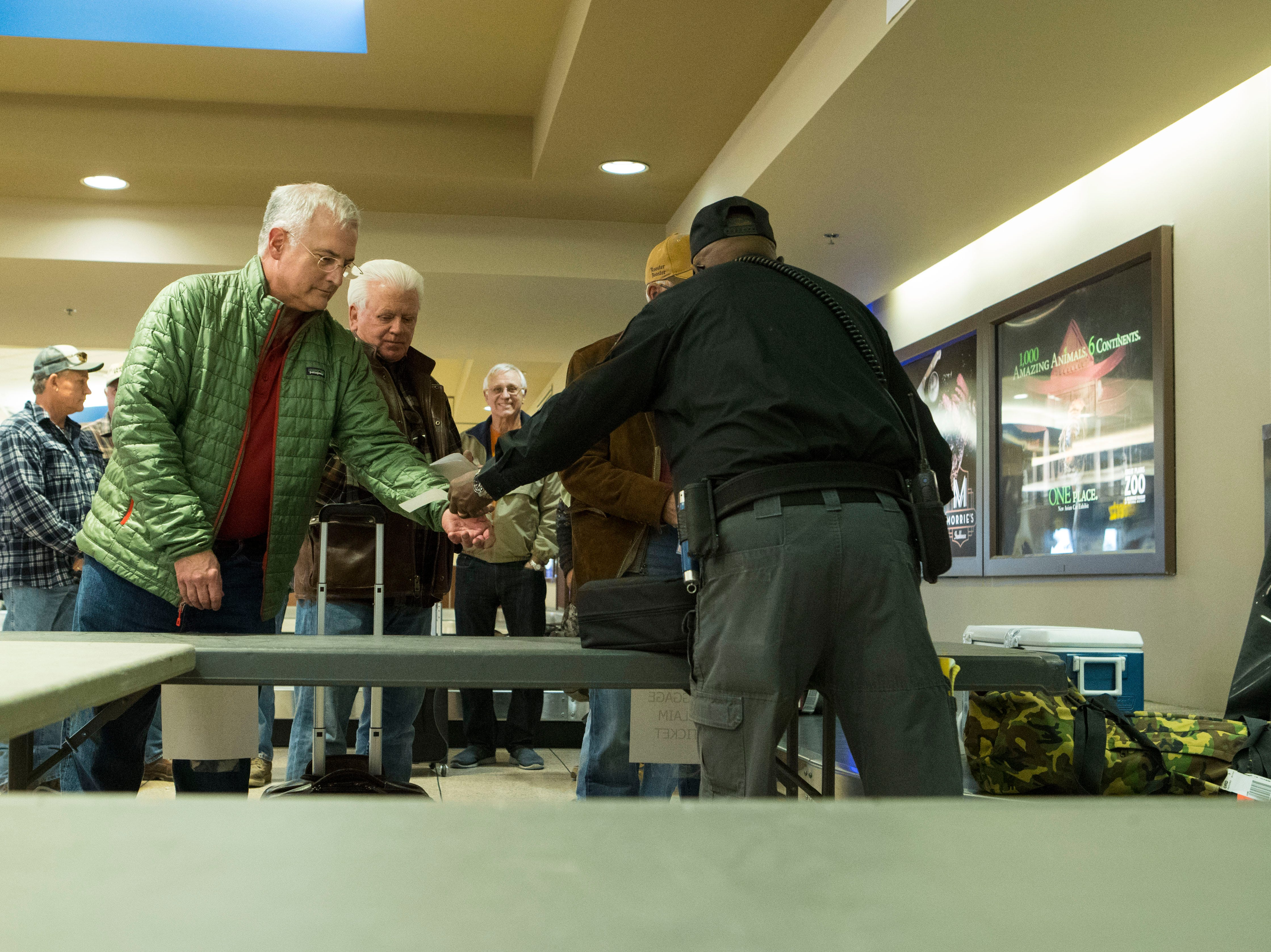 Pheasant hunters pick up their guns at security at the Sioux Falls Regional Airport Friday, Oct. 19, 2018.