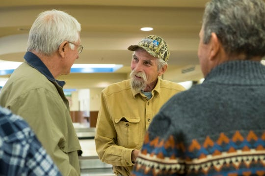Michael Drover speaks with fellow hunters while waiting for his luggage at Sioux Falls Regional Airport Friday, Oct. 19, 2018.