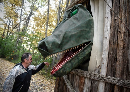 Ron Molitor checks on the large animated dinosaur he operates with pulleys and levers each night at Molitor's Haunted Acres in Sauk Rapids.