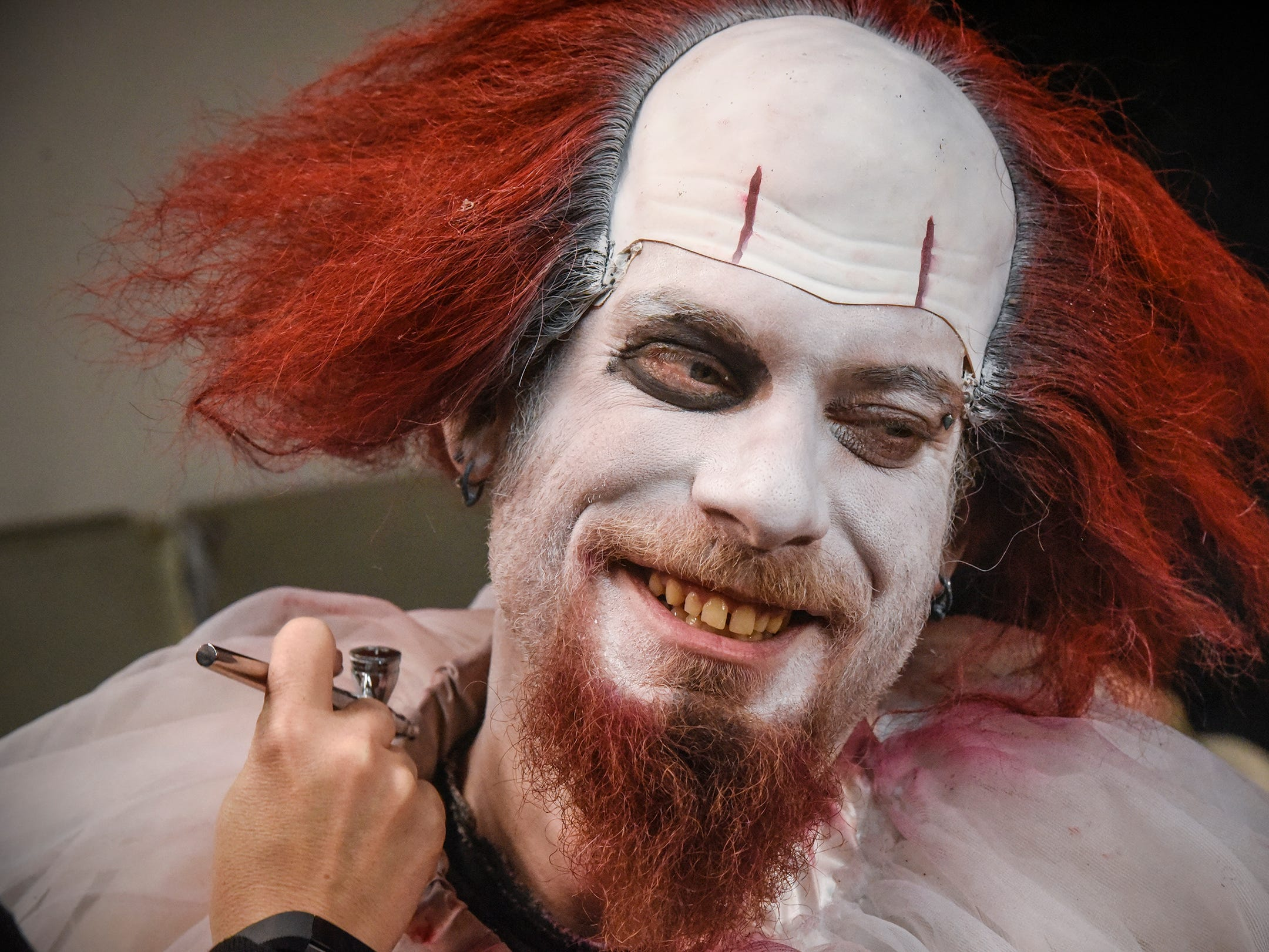 Cory Jolly smiles while sitting for makeup before performing as Pennywise Thursday, Oct. 18, at Molitor's Haunted Acres in Sauk Rapids.