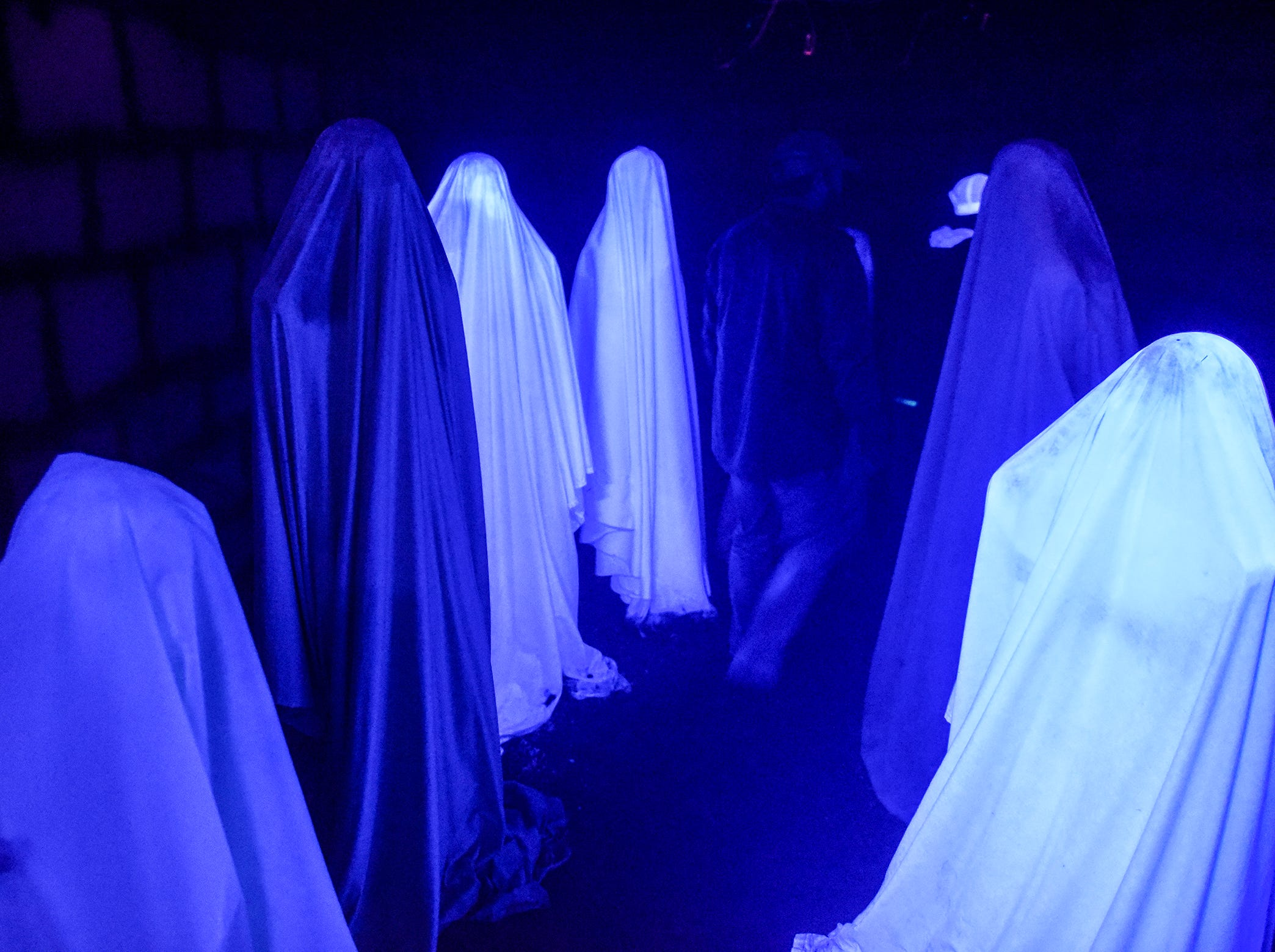 Visitors walk through a room Thursday, Oct. 18, at Molitor's Haunted Acres in Sauk Rapids.