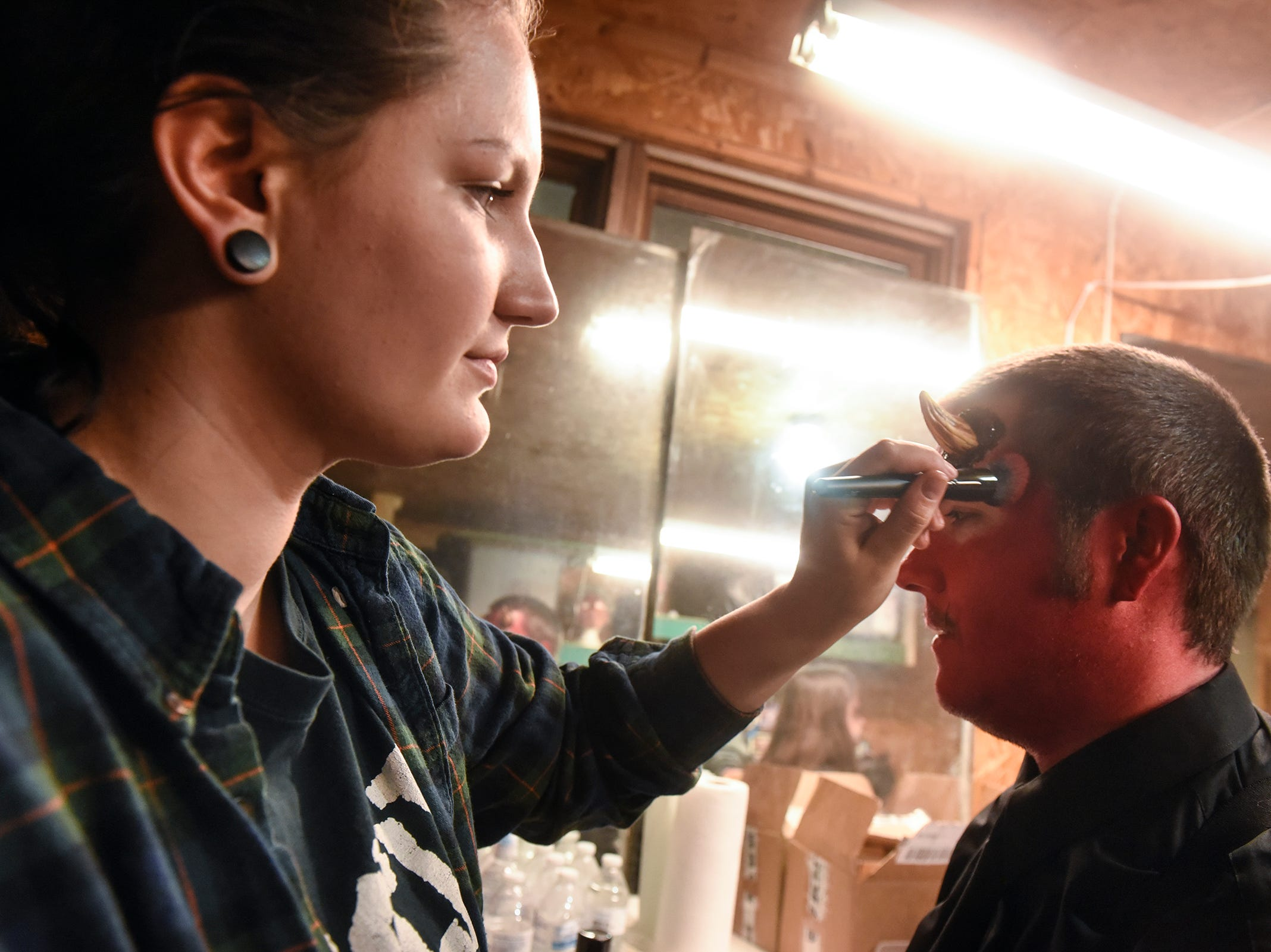 Taylor Froelich applies makeup to Treci King, who performs the part of Satan, Thursday, Oct. 18, at Molitor's Haunted Acres in Sauk Rapids.