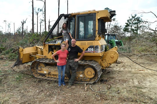 Nathan and Kelly Bunting pose with their daughter Norah on the bulldozer that kept them safe during Hurricane Michael.