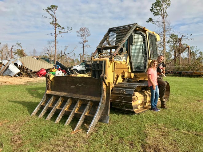 Nathan and Kelly Bunting and their dog Roxie stand next to the bulldozer they took refuge in during Hurricane Michael.
