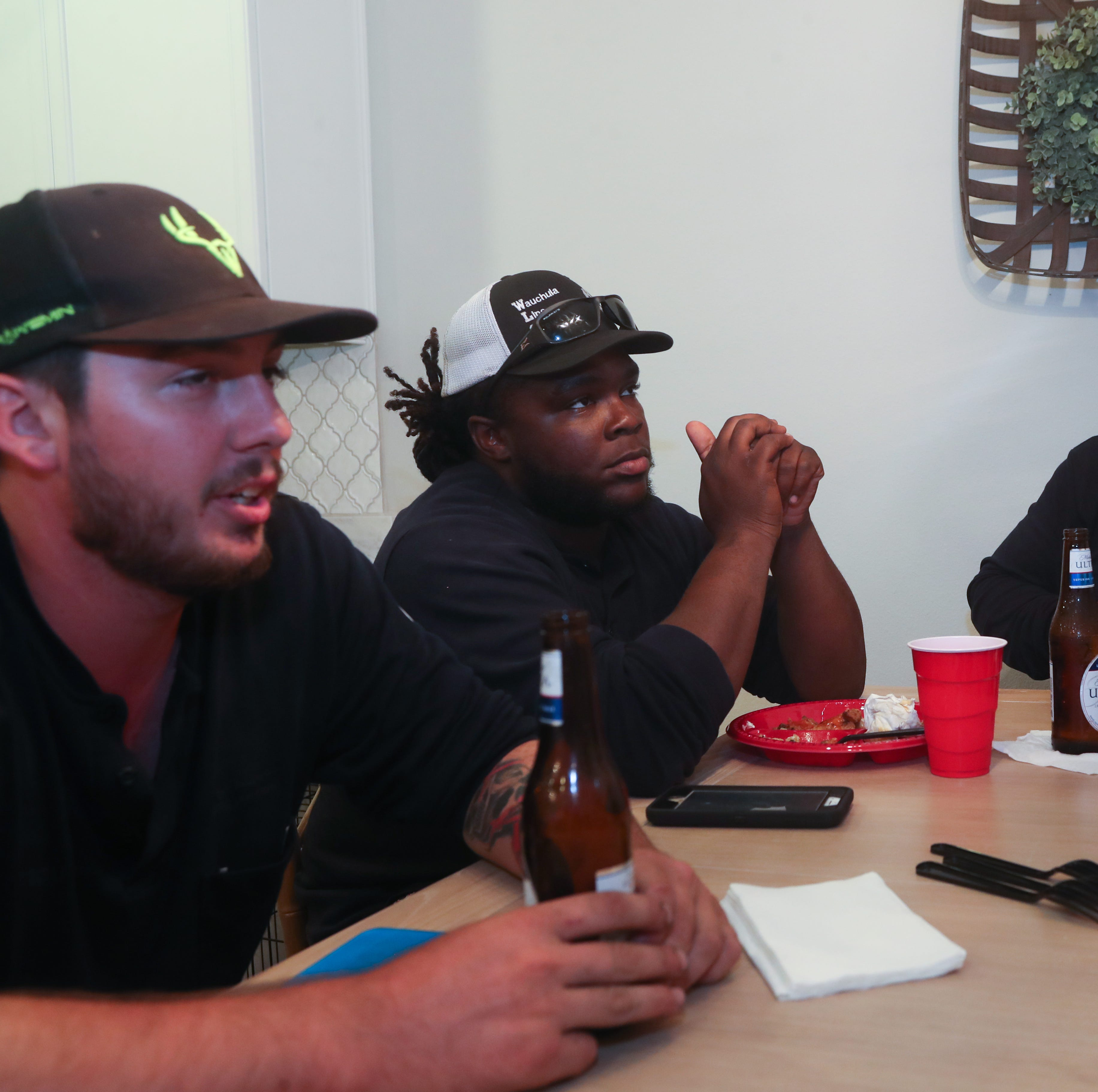 Dalton Garza, Debo McMillian and Jose Peña, apprentice linemen, eat dinner in the home of David and Ashley Bentley in the Ox Bottom Crest subdivision in Tallahassee, Fla. Thursday, Oct. 18, 2018.