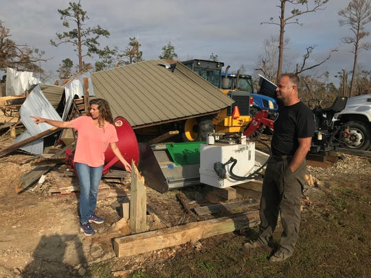 Kelly and Nathan Bunting examine the wreckage outside their home from Hurricane Michael.