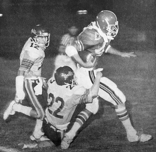 """Running back Rich Cunningham vividly demonstrates in the 1981 photo why coach Billy Livings nicknamed him """"Garbage Truck."""" """"He said that I wasn't really fast,"""" Cunningham recalled. """"And when I ran, it looked like the doors are flying open, but there are usually two or three guys hanging on the back riding with me."""""""