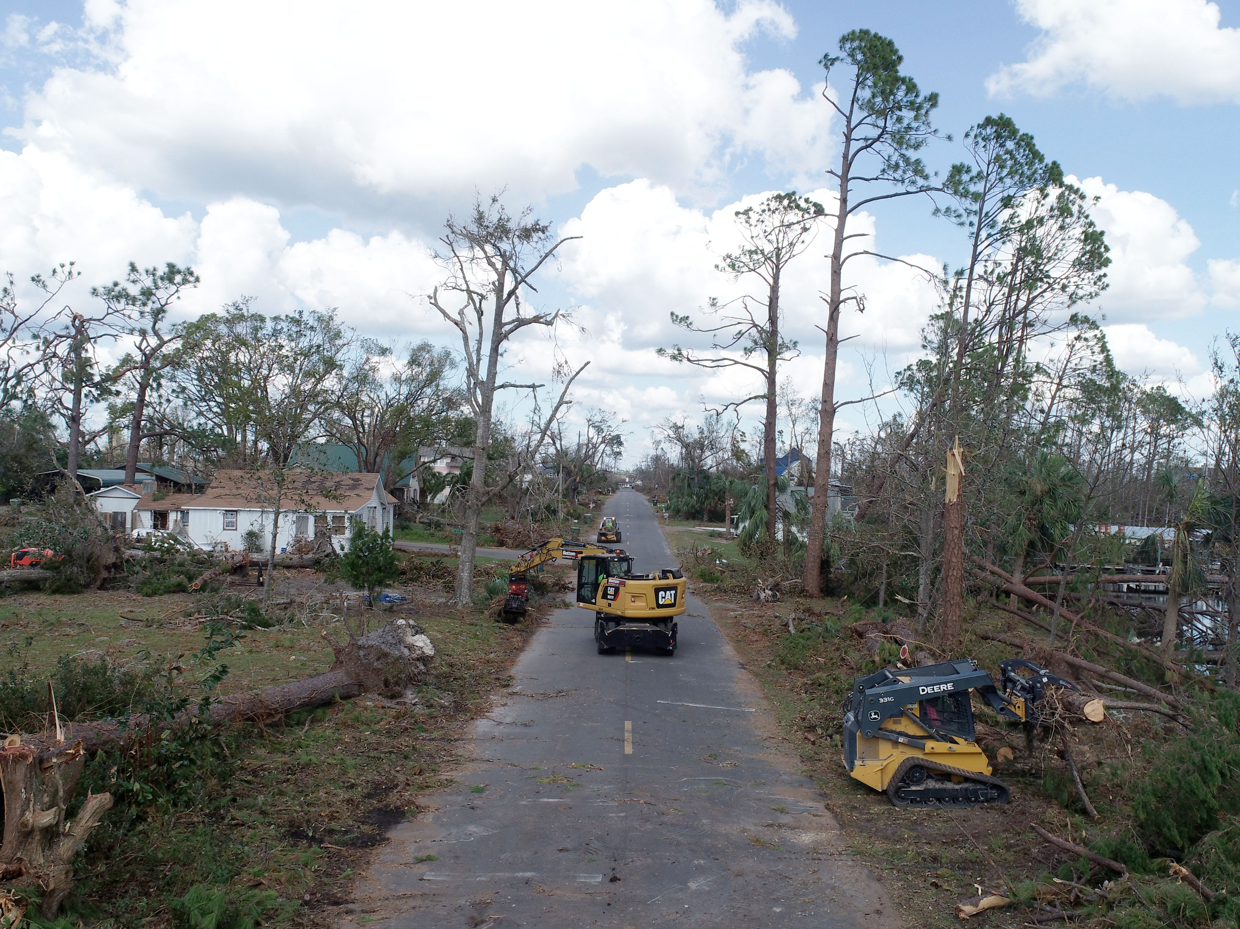 Crews haul away downed pine trees Wednesday, Oct. 17, 2018, in Lynn Haven, Florida, one week after Hurricane Michael made landfall in Florida's Panhandle.