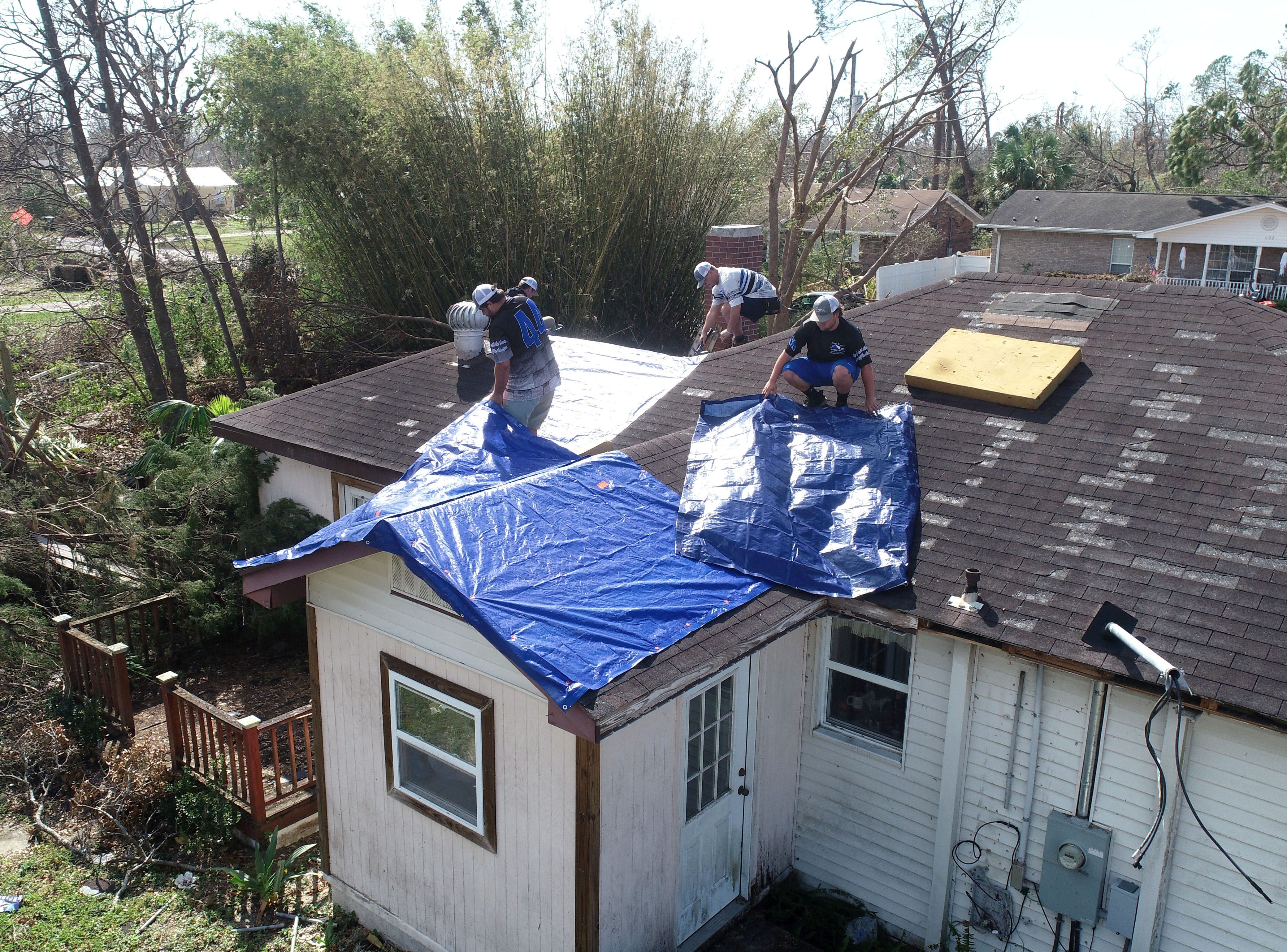 Workers place tarps on the roof of a home Wednesday, Oct. 17, 2018, in Lynn Haven, Florida. Residents have been working to recovery from Hurricane Michael, one week after it made landfall in the Florida Panhandle.