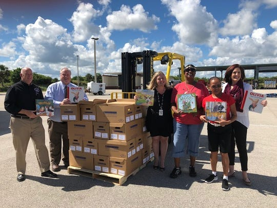 Schools Superintendent Mark Rendell (from left); Michael Kint, chief executive officer of United Way of Indian River County; Indian River County School Board member Laura Zorc; school bus drivers  Khawndice Colley and Sandra Jones; and School Board member Tiffany Justice show off some of the books they are sending to the Panhandle, where Hurricane Michael's impact has forced schools to close.